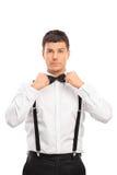 Hombre joven confiado que ajusta su corbata de lazo fotos de archivo libres de regalías