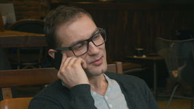Hombre joven confiado que habla en el teléfono móvil y que sonríe, dentro metrajes