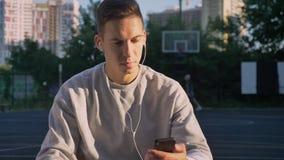 Hombre joven confiado que mecanografía en el teléfono, la música que escucha a través de los auriculares y mirando la cámara, gen almacen de video