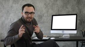 Hombre joven confiado que mira la cámara que habla de una manera muy confiada cerca de la pantalla de ordenador Visualización bla fotografía de archivo libre de regalías