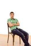 Hombre joven confiado que se sienta comfortablemente en una silla Fotos de archivo