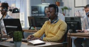 Hombre joven confiado que trabaja en un centro de atenci?n telef?nica