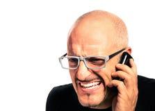 Hombre joven confuso durante una llamada de teléfono Imágenes de archivo libres de regalías