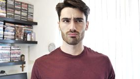 Hombre joven confuso o dudoso que rasguña su barbilla metrajes