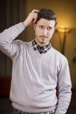 Hombre joven confuso o dudoso que rasguña su cabeza y que mira para arriba Imagen de archivo
