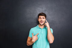 Hombre joven confuso que habla en el teléfono celular sobre el fondo blanco Fotos de archivo