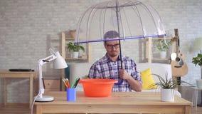 Hombre joven contrariedad debajo de un paraguas durante una inundación en el apartamento almacen de metraje de vídeo