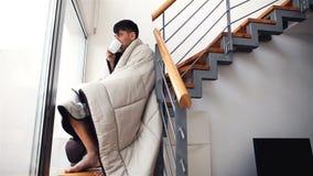 Hombre joven cubierto con el café de consumición de la manta que se sienta en las escaleras en casa almacen de video