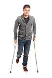 Hombre joven dañado en las muletas Foto de archivo libre de regalías
