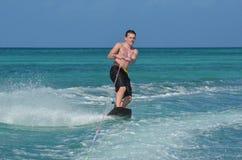 Hombre joven de Aruba que monta un Wakeboard en un día caliente imagen de archivo