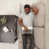 Hombre joven de Concenrated que usa el ordenador portátil en casa imagen de archivo libre de regalías