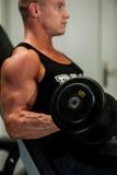 Hombre joven de Hnadsome que se resuelve con pesas de gimnasia en la aptitud - powe Imagenes de archivo