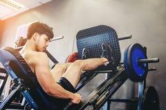 Hombre joven de la aptitud que ejercita usando el aparato de remar en el gimnasio Fotografía de archivo