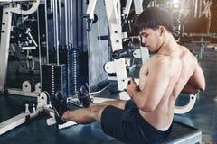 Hombre joven de la aptitud que ejercita usando el aparato de remar en el gimnasio Imagenes de archivo