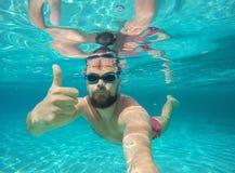 Hombre joven de la barba con los vidrios que se zambullen en un agua potable azul Fotografía de archivo