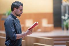 Hombre joven de la barba que lleva la camisa azul que ruega con la biblia en iglesia moderna Imágenes de archivo libres de regalías