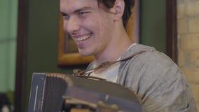Hombre joven de la habilidad que juega la sonrisa del acordeón Música alegre en el instrumento viejo Concepto popular almacen de video