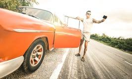 Hombre joven de la moda del inconformista con el tatuaje que toma el selfie con el coche del vintage durante el viaje por carrete imagen de archivo libre de regalías