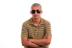 Hombre joven de la moda que sostiene las gafas de sol Imágenes de archivo libres de regalías