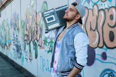 Hombre joven de la pared de la pintada con el casquillo Foto de archivo