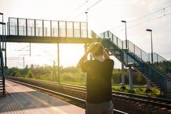 Hombre joven de la parte posterior, guardando sus manos en la cabeza de la diversión como su tren departured anterior El hombre e imagen de archivo libre de regalías