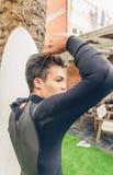 Hombre joven de la persona que practica surf con el wetsuit cerrado de la tabla hawaiana Fotografía de archivo