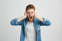 Hombre joven de la rabia enojada con los oídos cerrados de griterío de grito de la barba sobre el fondo blanco Imagenes de archivo