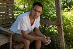 Hombre joven de la raza mixta que mira directamente en la c?mara, asentada en un oscilaci?n del patio trasero con el fondo del ve imagen de archivo