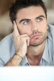 Hombre joven de la reflexión que mira hacia arriba foto de archivo