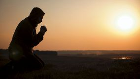 Hombre joven de la silueta que ruega afuera en la puesta del sol hermosa El var?n pide consuelo del hallazgo de la ayuda en la fe almacen de video