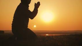 Hombre joven de la silueta que ruega afuera en la puesta del sol hermosa El var?n pide consuelo del hallazgo de la ayuda en la fe almacen de metraje de vídeo