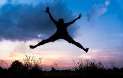 Hombre joven de la silueta que salta sobre campo del arroz Foto de archivo
