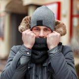 Hombre joven de moda en una chaqueta elegante del invierno y cubiertas del sombrero imágenes de archivo libres de regalías