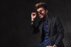 Hombre joven de moda que presenta en fondo oscuro del estudio mientras que mar Fotografía de archivo libre de regalías