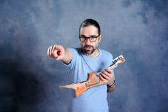 Hombre joven de pelo largo con la guitarra de la cartulina Fotos de archivo