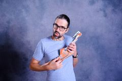 Hombre joven de pelo largo con la guitarra de la cartulina Foto de archivo