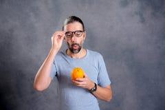 Hombre joven de pelo largo con la naranja Imagen de archivo