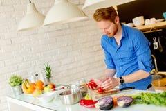 Hombre joven de Redhair que cocina la comida imágenes de archivo libres de regalías