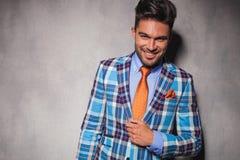 Hombre joven de risa en traje a cuadros y lazo anaranjado Fotografía de archivo libre de regalías