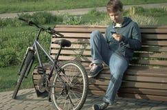 Hombre joven del adolescente con Smartphone y la bici imágenes de archivo libres de regalías