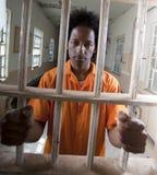Hombre joven del afroamericano detrás de barras Imágenes de archivo libres de regalías