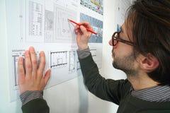 Hombre joven del arquitecto con las notas de la ropa de sport en su construcción p Fotografía de archivo