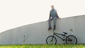 Hombre joven del cinematógrafo con la bicicleta en la hierba verde que se sienta en luz trasera