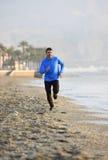 Hombre joven del deporte que corre en entrenamiento de la aptitud en la playa a lo largo de la madrugada del mar Foto de archivo