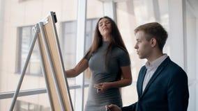 Hombre joven del director en mujer del traje y del experto en el vestido gris que juega oughts y cruces en el tablero blanco jefe almacen de video
