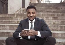 Hombre joven del empresario de negocio que sienta al aire libre las escaleras urbanas que trabajan y que usan el teléfono elegant fotografía de archivo