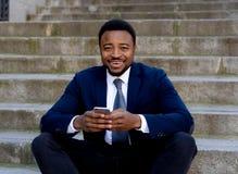 Hombre joven del empresario de negocio que sienta al aire libre las escaleras urbanas que trabajan y que usan el teléfono elegant imagenes de archivo