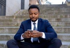 Hombre joven del empresario de negocio que sienta al aire libre las escaleras urbanas que trabajan y que usan el teléfono elegant imagen de archivo libre de regalías