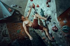 Hombre joven del escalador libre que sube el canto rodado artificial dentro imagenes de archivo
