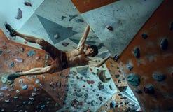 Hombre joven del escalador libre que sube el canto rodado artificial dentro imagen de archivo libre de regalías